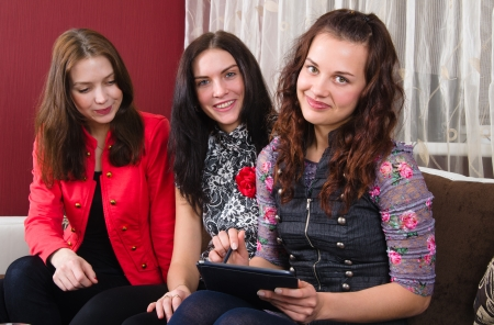 Three young women friends chatting at home and using laptop to look at new photo or browsing internet photo