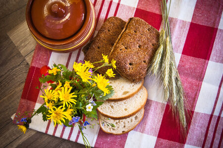 Still life with bread, flowers and pot photo