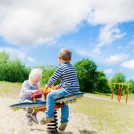 Boy and girl swinging on a swing, sunny day photo