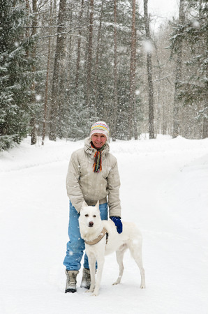 Woman with a dog on a walk in the woods during a snowfall photo