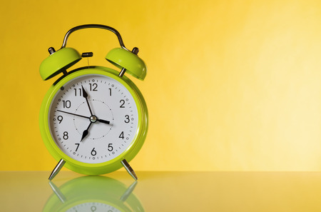 Green alarm clock, close up  A yellow background Imagens