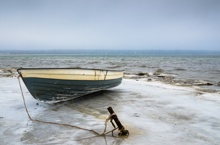 Fishing boat on the shore of the Baltic Sea. Winter landscape photo