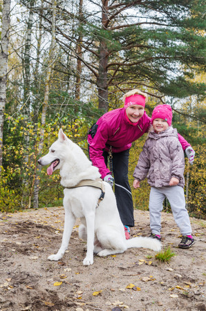 Granny with her granddaughter and a dog walk in autumn Park photo