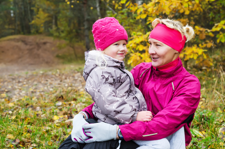 Grandmother with her granddaughter in the autumn park photo