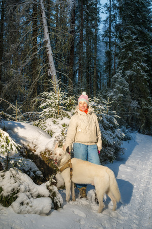 Woman with dog in winter forest on a walk photo