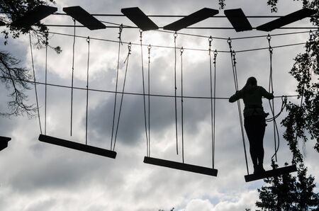 tether: Silhouette of the girl on Dangerous ropeway with tether in rope park