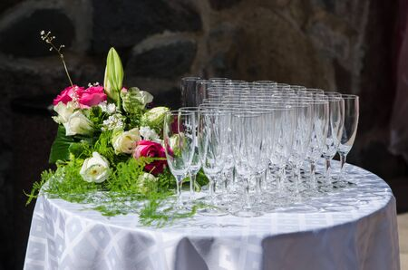 crystal glass: Bouquet of flowers and wine glasses for a wedding table Stock Photo