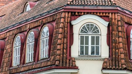 mansard: Mansard windows on a tile roof of the house in Tallinn, a close up