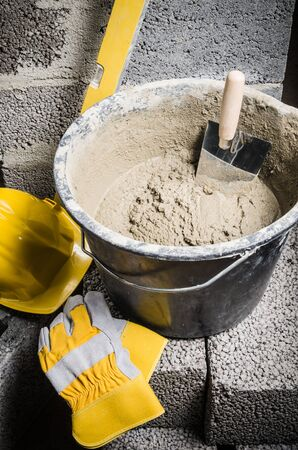 cement solution: Tools for bricklayer bucket with a solution and a trowel, close-up