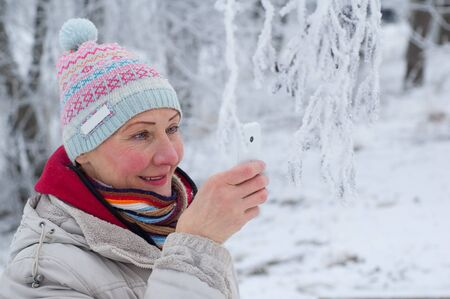 Portrait of an adult woman photographing on mobile phone in winter park photo