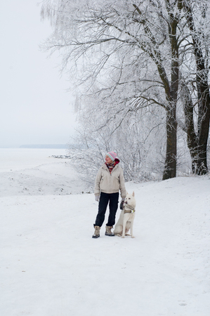Woman walking with a dog in winter photo