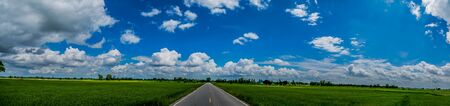 ranch background: Panorama Landscape. Green nature landscape of asphalt road between the cornfield and beautiful blue sky cloudy in the early morning. Phitsanulok, Thailand.