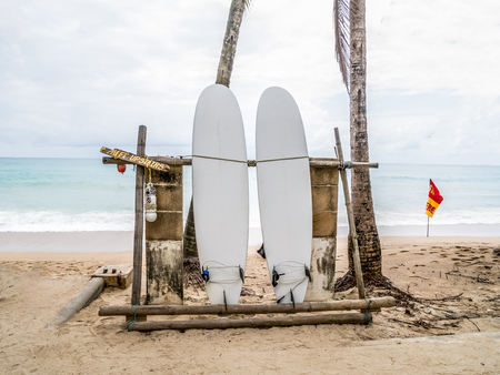 White surfboard abandoned on an empty sandy beach with waves in distance. At Kamala beach ,Phuket ,Thailand. Stock Photo