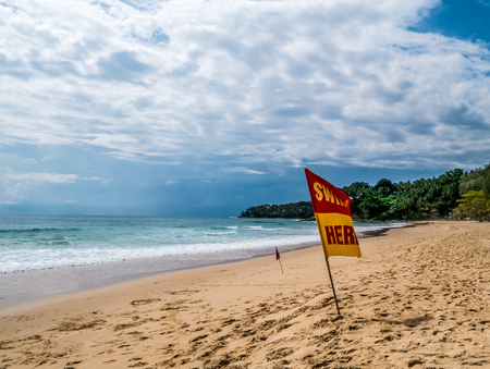 Swim here. Safety warning signs for tourists.  Blackground with island ,sky cloudy and windy. At Surin beach monsoon season. Phuket ,Thailand Stock Photo