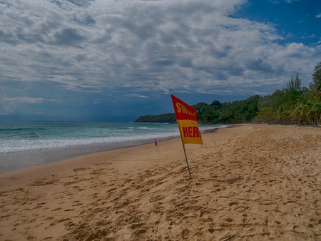 Swim here. Safety warning signs for tourists.  Blackground with island ,sky cloudy and windy. At Surin beach monsoon season. Thailand Stock Photo