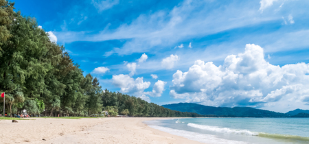 Tropical white sandy beach with turquoise clear water and palm trees. The backdrop is forest and beautiful blue sky cloudy.  Layan beach, Phuket,Thailand.