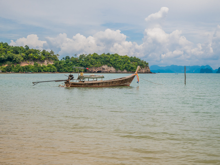 Small fishing boat of the villagers. Simple life, calm sleep, composed of trees. Located Yao Noi Island. Peaceful life at Koh Yao Noi, Phang Nga, Thailand. Background with cloudy blue sky