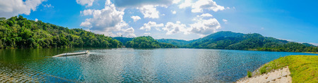 Panoramic landscape view of Bang Ward Dam ,Phuket ,Thailand. White fluffy clouds in the blue sky daylight. Sunshine background mountain and natural sky composition.