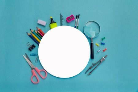 School supplies on blackboard background with round white paper ready for copy space