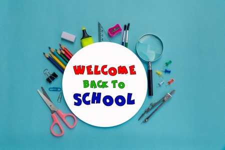 Round white paper with lettering welcome back to school and set of school equipment