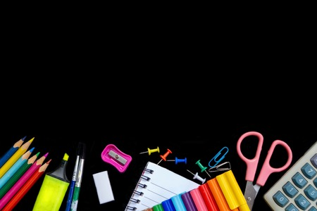 School supplies stationery on blackboard background ready for copy space