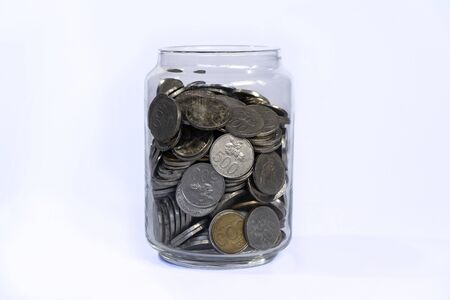 Saving idr coins in the glass bottle jar for finance investment or charity on white background