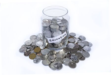 Saving idr coins in the glass bottle jar for education on white background 写真素材