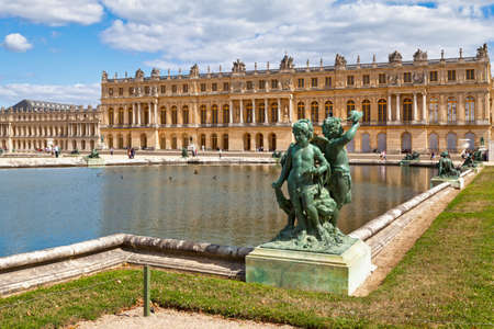Versailles, France - August 20 2017: Bronze statue of three cherubs placed on the edge of a basin of the Bassin du Midi in the gardens of Versailles, in front of the west facade of the Palace of Versailles.