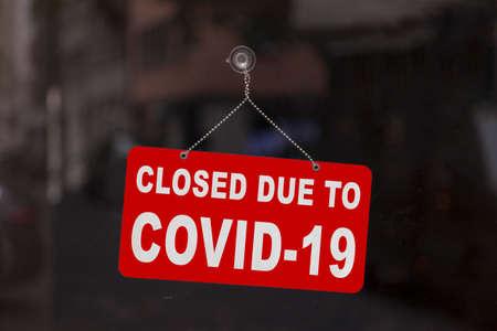 Nahaufnahme auf einem roten geschlossenen Schild im Schaufenster eines Geschäftes, das die Nachricht anzeigt