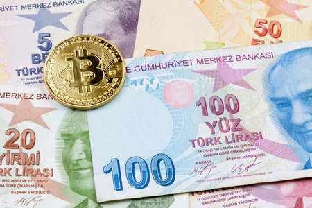 Close-up on a golden Bitcoin coin on top of a stack of Turkish lira banknotes.