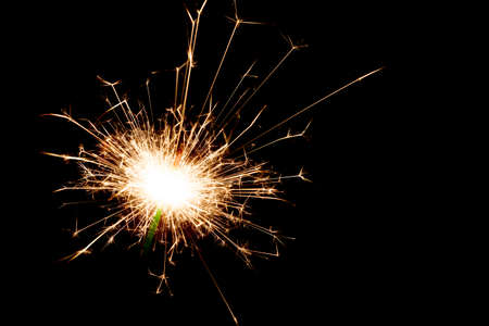 Close-up on a sparkler lit in the dark with copy space on the right.