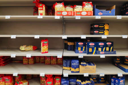 Paris, France - March 16 2020: Shelves of a supermarket normally filled with pasta packs nearly empty since entering stage 3 of the coronavirus pandemic plan.