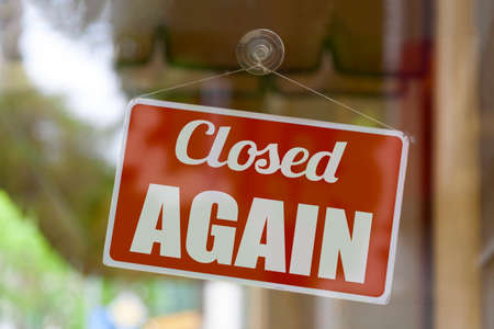 Close-up on a red open sign in the window of a shop displaying the message: Closed again.