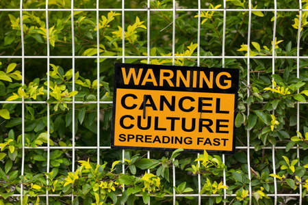 "Black and yellow warning sign on a fence stating ""Warning, cancel culture spreading fast""."