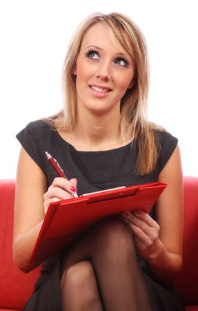 Young woman writing in red folder Stock Photo