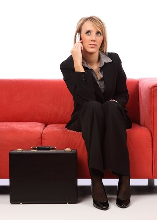 Business woman on mobile phone while sitting with briefcase