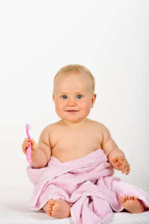 12 month old: 6-12 mesi di et� bambino avvolto in un asciugamano rosa dopo il bagno, � in possesso di uno spazzolino da denti rosa abituare i bambini a hygeine dentale in et� precoce Archivio Fotografico