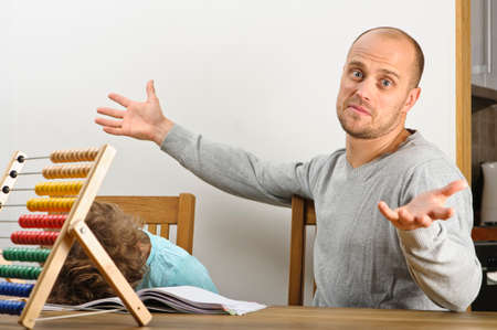 elementary age boy: Frustrated father thows up his hands in despair  Frustrated elementary age boy lays his head on his copy book  Stock Photo