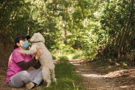 Woman wearing disposable medical face mask playing with poodle dog in the park during coronavirus outbreak. Pet walk.