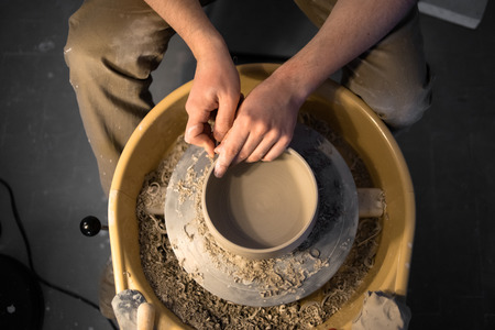 Hands of pottery artist works with earthenware on pottery wheel Stock Photo