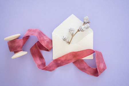 Silver bell pods peeps out of handcrafted little envelope with red ribbon on wooden coil on lilac table, top view Stock Photo