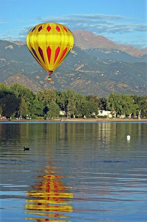 A hot air balloon floats over Prospect Lake in Colorado Springs, Colorado with Pikes Peak in the background Stock Photo