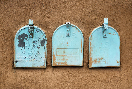 Faded blue mailboxes in a stucco wall Stock Photo