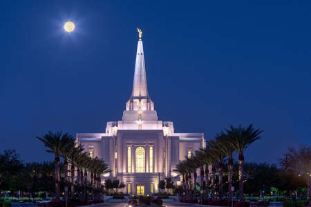The Harvest Moon low in the sky over the Latter Day Saints temple in Gilbert, Arizona shortly before sunrise.
