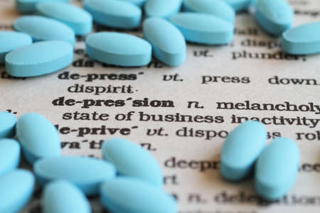 antidepressant: Depression. The word depression in text form, surrounded by anti-depressant pills