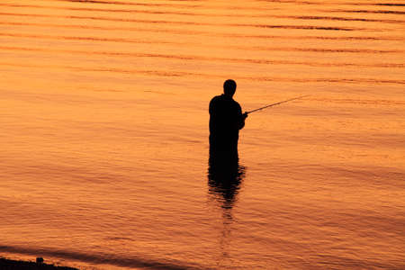 silhoutted: Solitude  A lone fisherman is silhoutted against the golden waters of a river