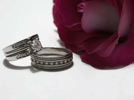 Photo of male and female diamond wedding rings next to a red rose.
