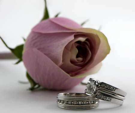 Photo of a mans and womans diamond wedding rings in front of a pink rose