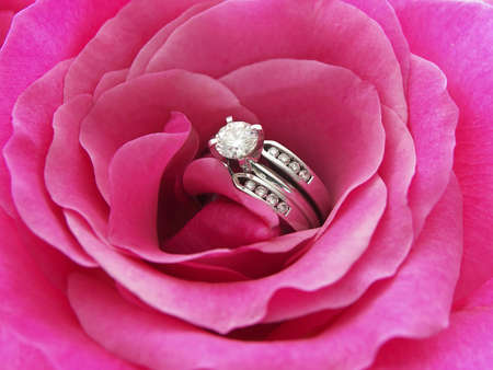 Photo of a diamond wedding ring in the center of a pink rose