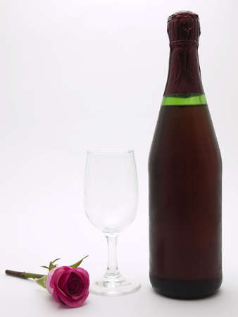 Photo of a bottle of champagne and glass with a rose laying next to them